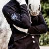 Schöne Frau mit Pferd und Turnierjacket in Schwarz mit Stass Elementen