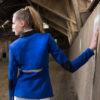 Junge Frau mit Reitsakko in Royalblau und Reißverschlüssen in einer Reithalle