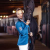 Schöne Reiterin und Pferd im auffälligen Turnierjacket in Petrol