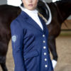 Junge Frau mit Pferd und Reitjacket in Navyblau
