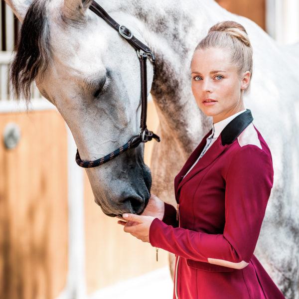Sinnliche Frau und Pferd mit Tunriersakko im Farbton Berry