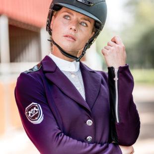 Schöne Frau mit Pferd und auffälligem Turnierjackett in Lila
