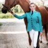 Schöne Frau mit Pferd und auffälligem Turnierjackett in Türkis
