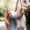Schöne Frau mit Schimmel Pferd und modernem Turnierjacket in Grau