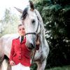 Schöne Frau mit Schimmel Pferd in einem auffälligen Reitblazer