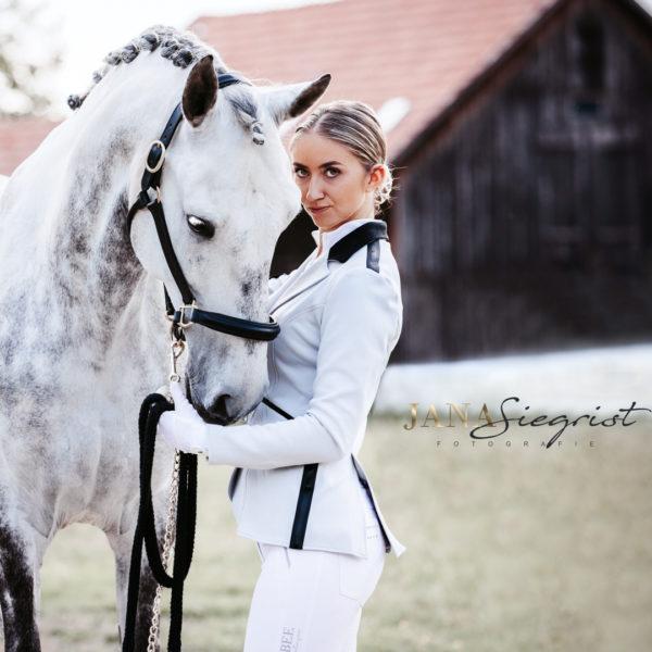 Anmutige Frau mit Schimmel Pferd und Turnieroutfit