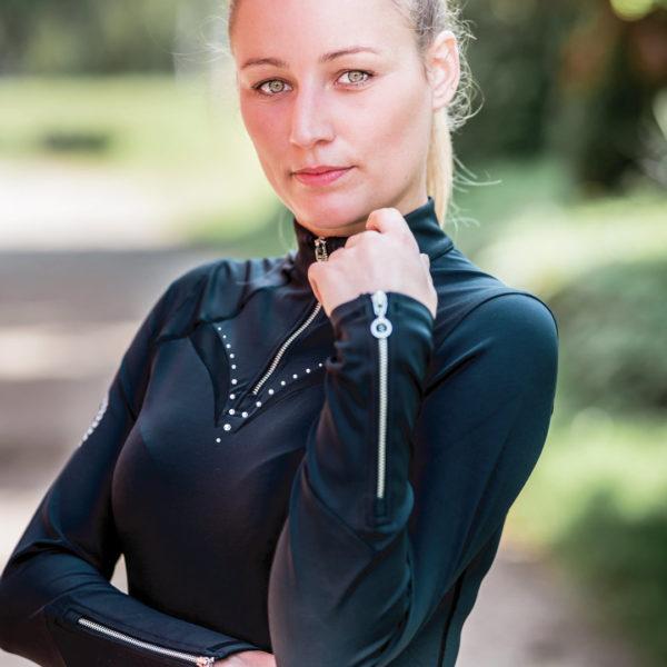 Junge Frau mit elegantem Longsleeve in Schwarz für den Reitsport