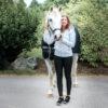 Lachende Frau mit Pferd in einem Hellgrauem Kapuzenpullover