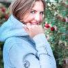 Lachende Frau mit Hellgrauem Kapuzenpullover