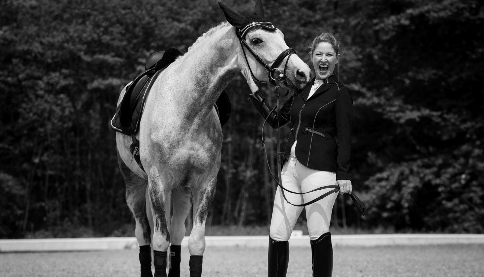 Glückliche Frau mit Tunrnieroutfit und schönem Pferd am lachen