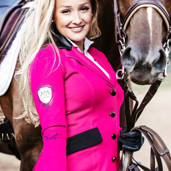 Strahlende Frau mit Pferd und Pinkem Turniersakko