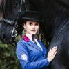 Sinnliche Frau mit schwarzem Pferd und besonderem Reitjacket