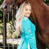 Schöne Frau mit ausgefallenem und hochwertig verarbeitetem Blazer für ein Reitturnier mit Pferd.